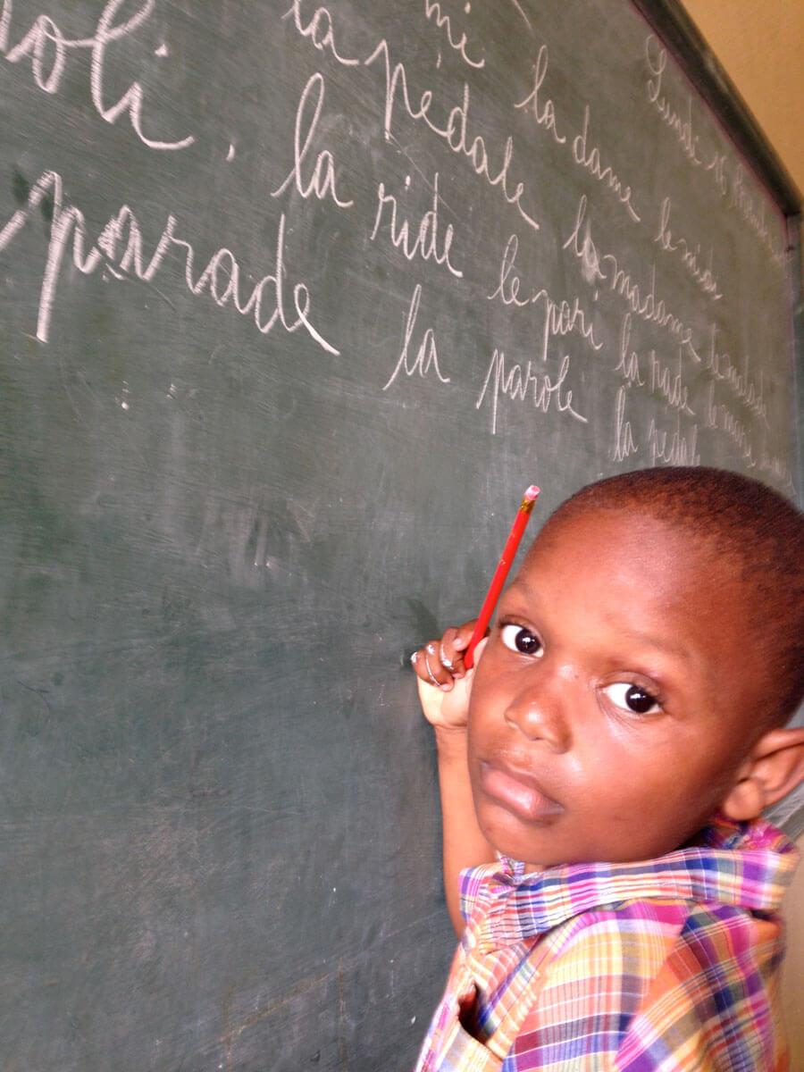 Boy writing on chalkboard